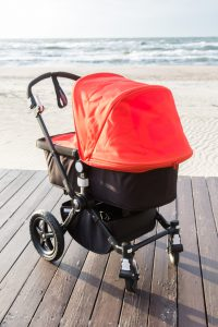 Red and black baby stroller on the sea background.